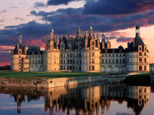 French Chateau de Chambord; twilight, sun and shadow; ornate palace reflected in water with dark clouds overhead and behind, there is just a tuch of pink in the clouds.